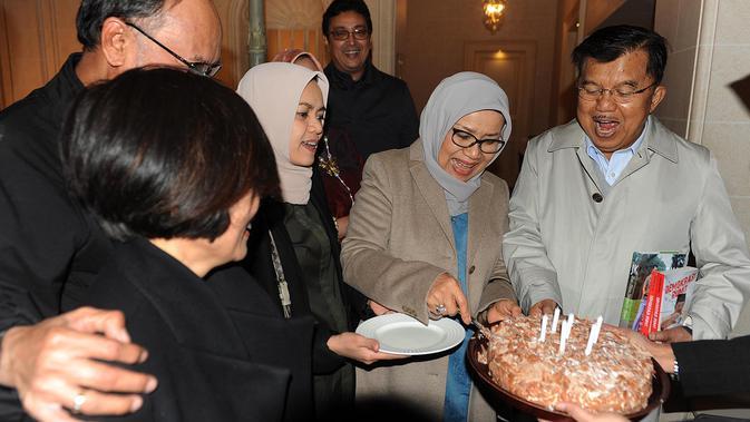 Mufidah Kalla memotong kue dan memberikannya kepada Wakil Presiden Jusuf Kalla seusai acara kejutan ulang tahun ke-77 di Jenewa, Swiss, Rabu (15/5/2019). JK berkunjung ke Swiss untuk menghadiri sebuah pertemuan yang diinisiasi PBB dengan bahasan penanganan bencana. (Liputan6.com/Tim Media Wapres)