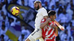 Striker Real Madrid, Karim Benzema, berebut bola dengan bek Girona, Juanpe Ramirez, pada laga La Liga di Stadion Santiago Bernabeu, Madrid, Minggu (17/2). Madrid kalah 1-2 dari Girona. (AFP/Gabriel Bouys)