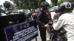 Petugas dari Korps Brimob memeriksa surat keterangan warga saat penyekatan di Jalan Lenteng Agung Raya, Jakarta, Selasa (6/7/2021). Petugas hanya mengizinkan warga yang memiliki kepentingan esensial atau mendesak bisa melintas jalan Lenteng Agung Raya. (Liputan6.com/Helmi Fithriansyah)