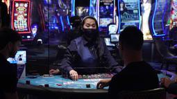 Para pengunjung bermain blackjack saat pembukaan kembali hotel dan kasino Bellagio di Las Vegas, Nevada, Amerika Serikat, Kamis (4/6/2020). Kasino di Nevada diizinkan kembali beroperasi setelah penutupan sementara untuk mencegah penyebaran virus corona COVID-19. (AP Photo/John Locher)