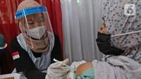 Vaksinator menyuntikkan vaksin COVID-19 kepada warga di Kampung Tangguh Jaya Cideng, Jakarta, Sabtu (10/4/2021). Adapun sasaran program vaksinasi massal ini kaum lanjut usia (lansia) dan pelayan publik yang sering berinteraksi dengan masyarakat. (Liputan6.com/Herman Zakharia)