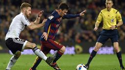Lionel Messi dibayangi pemain Valencia, Shkodran Mustafi (kiri) pada leg pertama semifinal  Copa del Rey (King's Cup) di Stadion Camp Nou, Barcelona, Kamis (4/2/2016) dini hari WIB. (AFP/Lluis Gene)