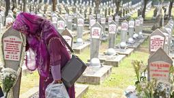Warga mencium batu nisan di makam Hasri Ainun Besari yang bersebelah dengan makam sang suami,  Presiden ke-3 RI BJ Habibie di TMP Kalibata, Jakarta, Jumat (13/9/2019). Sesuai permintaannya semasa hidup, BJ Habibie dimakamkan bersebelahan dengan mendiang istrinya Ainun. (Liputan6.com/Herman Zakharia)