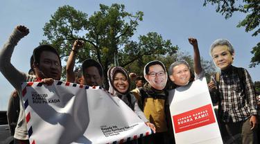 Para aktivis menggunakan topeng sejumlah kepala daerah saat melakukan aksi di depan Istana Merdeka, (16/8/14). (Liputan6.com/Miftahul Hayat)