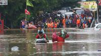Warga melintasi banjir  yang merendam jalan Raya KH Hasyim Ashari, Ciledug ,Tangerang, Rabu (1/1/2020). Banjir setinggi dada orang dewasa membuat jalur penghubung Tangerang ke Jakarta tersebut terputus tidak dapat dilintasi. (Liputan6.com/Angga Yuniar)