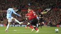 Penyerang Manchester City, Bernardo Silva, mencetak gol ke gawang Manchester United pada laga Premier League di Stadion Old Trafford, Rabu, (24/4). Manchester United takluk 0-2 dari Manchester City. (AP/Jon Super)