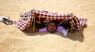 Seorang pria menutupi kepalanya saat dikubur dengan pasir gurun di Siwa, Mesir, 12 Agustus 2015. Terapi mengubur diri di dalam pasir gurun saat terik matahari diyakini dapat menyembuhkan rematik, sakit sendi, dan impotensi seksual. (REUTERS/Asmaa Waguih)