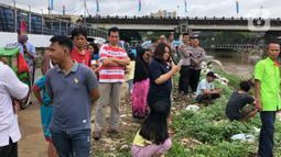 Warga bersama personel kepolisian berkumpul di bantaran Sungai Ciliwung, Jakarta, Selasa (25/2/2020). Adanya seorang warga yang hanyut saat berenang di tengah luapan Sungai Ciliwung tersebut mengundang perhatian warga serta petugas yang mencari keberadannya. (Liputan6.com/Immanuel Antonius)