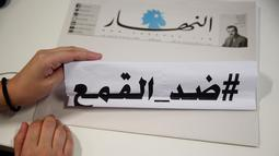 "Seorang wartawan surat kabar harian An-Nahar, memegang kertas dengan kata-kata Arab yang berbunyi: ""Terhadap penindasan,"" pada salinan surat kabar dengan halaman kosong tanpa berita, di kantor An-Nahar, Beirut, Kamis (11/10). (AP/Hussein Malla)"