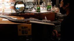 Pekerja menikmati lintasan mobil balap mainan yang dipasang di sebuah bar di Praha, Republik Ceko, 15 Oktober 2020. Lintasan di atas meja bar itu cukup menghibur untuk menghabiskan waktu di tengah larangan buka restoran dan hanya menerima pesanan untuk dibawa pulang saja. (AP Photo/Petr David Josek)