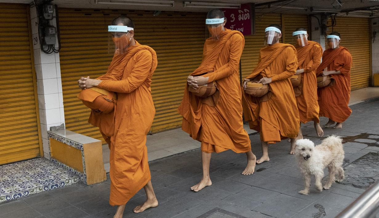 Para biksu Buddha memakai pelindung wajah untuk melindungi diri dari virus corona COVID-19 saat mengumpulkan sedekah di Bangkok, Thailand, Selasa (31/3/2020). Hingga 30 Maret 2020 sore, jumlah kasus COVID-19 di Thailand sebanyak 1.524 positif, 229 sembuh, dan 9 meninggal. (AP Photo/Sakchai Lalit)