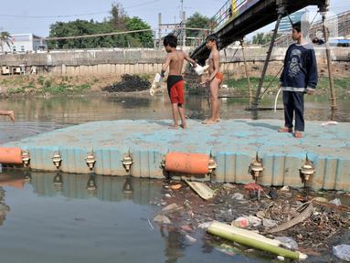 Anak-anak berenang di Kanal Banjir Barat, Jakarta, Minggu (3/11/2019). Banyaknya sampah yang menggenang tidak menghentikan keseruan anak-anak berenang di Kanal Banjir Barat. (merdeka.com/Iqbal Nugroho)