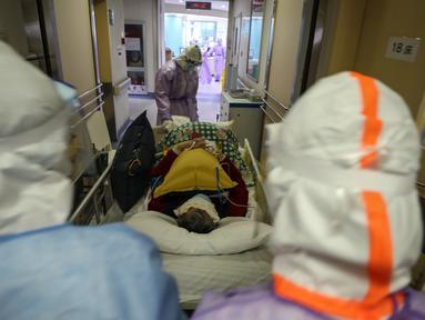 Petugas medis memindahkan seorang pasien yang terinfeksi virus corona COVID-19 di rumah sakit Palang Merah di Wuhan pada 28 Februari 2020. Virus corona baru, Covid-19, telah mewabah hingga ke lebih dari 60 negara dimana dari kasus-kasus infeksi, ada lebih dari 3.000 kematian yang terjadi.  (STR/AFP)