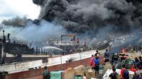 Sejumlah pekerja dan petugas pemadam kebakaran mencoba memadamkan api kapal nelayan di pelabuhan Benoa, Denpasar, Bali, Senin (9/7). Kebakaran yang menghanguskan puluhan kapal diperkirakan mencapai kerugian Rp 3 - 4 miliar. (AFP Foto / Sonny Tumbelaka)