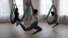 Para murid melakukan gerakan aerial yoga atau yoga udara di Aerial Jooga Studia, Kelapa Dua, Tangerang, Banten, Minggu (10/10/2021). Di masa pandemi, peminat olahraga yang berasal dari Amerika Serikat ini meningkat lebih dari 60 persen. (merdeka.com/Arie Basuki)