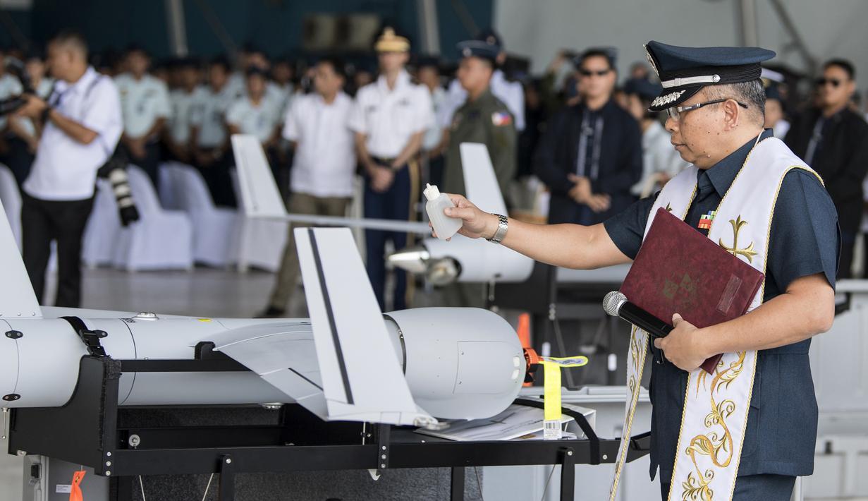 Seorang pendeta militer memberkati drone ScanEagle Umanned Aerial Vehicles (UAV) dalam upacara serah terima di Pangkalan Udara Villamor, Manila, Filipina, Selasa (13/3). Filipina mendapat enam drone canggih dari hibah Amerika Serikat. (TED ALJIBE/AFP)