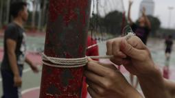 Warga mengikat jaring net saat olahraga voli di Kawasan Monumen Nasional, Jakarta, Rabu (13/2). Monas merupakan salah satu lokasi yang kerap dijadikan ruang olahraga bagi warga ibukota. (Bola.com/M. Iqbal Ichsan)
