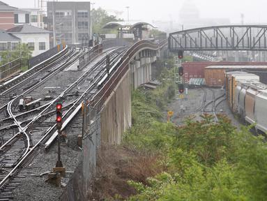 Sebuah kereta barang CSX keluar dari rel di bagian timur laut Washington, Minggu (1/5) waktu setempat. Kereta ini menumpahkan zat kimia berbahaya dekat stasiun bawah tanah dan mengganggu lalu lintas kereta api bawah tanah. (Andrew BIRAJ /AFP)