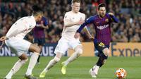 Striker Barcelona, Lionel Messi, berusaha melewati pemain Manchester United pada laga Liga Champions 2019 di Stadion Camp Nou, Selasa (16/4). Barcelona menang 3-0 atas Manchester United. (AP/Joan Monfort)