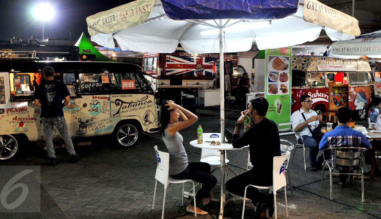 Pengunjung menunggu pesanan makanan yang dijual di atas mobil van di area Food Truck Convoy dalam ajang Indonesia International Motor Show (IIMS) 2015 di JIExpo Kemayoran, Jakarta, Selasa (25/8/2015). (Liputan6.com/Andrian M Tunay)