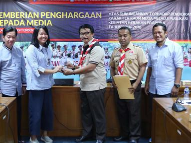 Ketua Kwarnas Gerakan Pramuka Adhyaksa Dault menyerahkan plakat kepada Redaktur Eksekutif Liputan6.com Irna Gustiawati di Gedung Kwarnas Gerakan Pramuka, Gambir, Jakarta Pusat, Senin (24/9). (Liputan6.com/Immanuel Antonius)