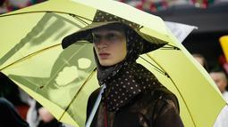 Seorang model mengenakan rancangan desainer Raf Simons dalam acara Men's Fashion Week di New York, Selasa (11/7). Topi dan payung menjadi aksesoris andalan Raf Simons dalam rancangannya. (AP/Frank Franklin)