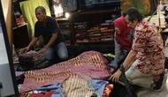 Pengunjung memilih koleksi batik yang dipamerkan pada Interior and Craft (ICRA) Exhibition 2019 yang dihelat di Hall A Jakarta Convention Center (JCC), Senayan, Jakarta, Minggu (6/10/2019). Ratusan motif batik dari berbagai daerah dipamerkan pada ajang ini. (Liputan6.com/Helmi Fithriansyah)