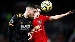 Gelandang Manchester United, Daniel James, duel udara dengan pemain Wolverhampton Wanderers, Matt Doherty, pada laga Premier League di Stadion Old Trafford, Sabtu (1/2/2020). Kedua tim bermain imbang tanpa gol. (AP/Martin Rickett)