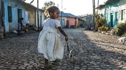 Seorang anak bermain di sebuah jalan di Kota Gondar, Ethiopia pada 09 November 2020. (Photo by EDUARDO SOTERAS / AFP)