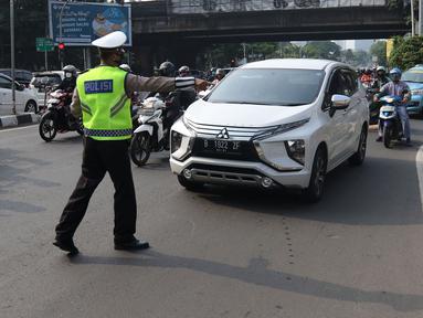 Polisi menghentikan mobil saat pemberlakuan ganjil genap di kawasan Fatmawati, Jakarta, Senin (25/10/2021). Pemberlakuan ganjil genap di DKI Jakarta diperluas menjadi 13 titik. (Liputan6.com/Herman Zakharia)