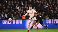 Dani Alves dijatuhkan Luke Shaw pada leg kedua, babak 16 besar Liga Champions yang berlangsung di Stadion Parc des Princes, Paris, Kamis (7/3). Man United menang 3-1 atas PSG. (AFP/Anne-Christine Poujoulat)