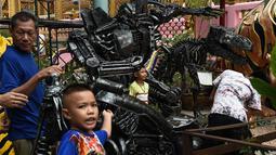 Pengunjung berpose di dekat patung logam 'Transformers' di kuil Buddha Wat Tha Kien di Nonthaburi, Thailand (18/6). (AFP Photo/Lillian Suwanrumpha)