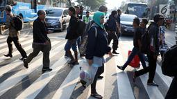 Warga melintasi Pelican Crossing di sekitar Halte Transjakarta Gelora Bung Karno, Jakarta, Jumat, (30/11). Ada tiga jembatan penyeberangan orang (JPO) di Jalan Jenderal Sudirman, Jakarta, yang sedang direvitalisasi. (Liputan6.com/Helmi Fithriansyah)