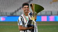 Striker Juventus, Cristiano Ronaldo, mengangkat trofi juara Serie A musim 2019-20 di Stadion Allianz, Sabtu (1/8/2020). CR7 berhasil membawa Juventus merengkuh gelar Liga Italia kesembilan secara beruntun. (Photo by Isabella BONOTTO / AFP)