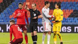 Wasit memberikan kartu merah kepada pemain Swiss, Nico Elvedi, saat melawan Spanyol pada laga UEFA Nations League di Stadion St. Jakob-Park, Minggu (15/11/2020). Kedua tim bermain imbang 1-1. (Alessandro della Valle/Keystone via AP)