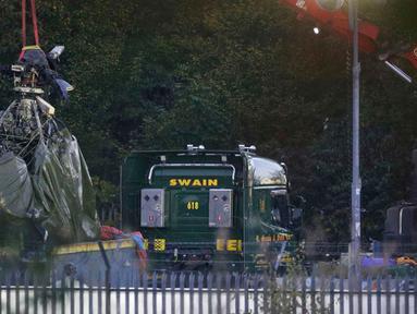 Crane mengevakuasi bangkai helikopter dari lokasi kecelakaan yang menewaskan pemilik Leicester City Vichai Srivaddhanaprabha di Leicester, Inggris, Kamis (1/11). Kondisi helikopter terlihat rusak parah dengan bekas terbakar api. (Aaron Chown/PA via AP)