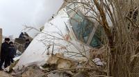 Petugas setempat memeriksa sekitar pesawat kargo Turki yang jatuh di daerah perumahan di Bishkek, Kyrgyzstan (16/1). Menurut otoritas bandara, pesawat Turkish Airlines tersebut seharusnya singgah di Bandara Manas. (AP Photo/Vladimir Voronin)