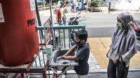 Seorang anak didampingi orangtua mencuci tangan terlebih dahulu sebelum mengikuti program BIAS di Kantor Kelurahan Tamansari, Jakarta, Selasa (24/11/2020). BIAS dipusatkan di kantor kelurahan masing-masing wilayah. (merdeka.com/Iqbal S. Nugroho)