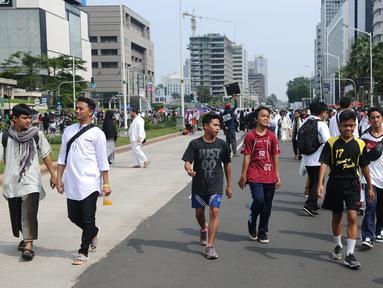 Sejumlah remaja beraktivitas di antara peserta Reuni 212 saat Car Free Day (CFD) di kawasan Jakarta, Minggu (2/12). Warga tetap memadati area Car Free Day  dari Bundaran HI-Sudirman meskipun ada aksi Reuni 212. (Liputan6.com/Angga Yuniar)