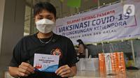 Atlet Bulutangkis Apriyani Rahayu menunjukkan kartu vaksin di Rumah Sakit Olahraga Nasional, Jakarta, Jumat (12/3/2021). Kemenpora bersama Kemenkes melakukan vaksinasi COVID-19 dosis ke-2 kepada insan olah raga nasional dengan menyasar 820 orang secara bertahap. (Liputan6.com/Herman Zakharia)