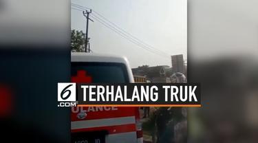 Jalanan dipenuhi truk-truk di sekitar Parung Panjang, Bogor. Jalanan yang macet membuat sebuah ambulans menjadi korban kemacetan. Ambulans tersebut tak bisa lewat karena terhalang truk.