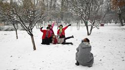 Sejumlah wanita berpose saat salju turun di sebuah taman di Beijing (16/12/2019). Pada pukul 7 Senin pagi, 42 penerbangan telah dibatalkan di Bandara Internasional Ibukota Beijing. (AFP Photo/Wang Zhao)