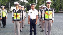 Pria bernama Polisi (Kemeja putih) berbaris dan anggota kepolisian di Polres Pasuruan (21/11). Sebelumnya, Polisi bekerja sebagai kuli bangunan. Akibat viral di medsos karena namanya yang unik, Polisi ditugaskan di Satlantas Polres Pasuruan. (AFP Photo)