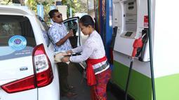 Petugas dengan pakaian adat mengisi bahan bakar minyak (BBM) ke sebuah mobil di SPBU, Bali, Rabu (10/10). Petugas SPBU mengenakan pakaian adat Bali untuk menyambut pertemuan tahunan IMF dan Bank Dunia. (Liputan6.com/Angga Yuniar)