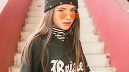 Kaus hitam seakan sudah menjadi andalan Sara Fajira dalam berpenampilan. Untuk menambah kesan kece, ia memadukan kaus turtleneck bermotif garis dengan kaus hitam over size. Tak lupa, ia juga memakai topi dan kacamata keren. (Liputan6.com/IG/@sarafajira)