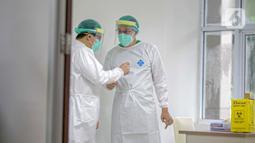 Dua vaksinator berbincang saat melakukan vaksinasi COVID-19 kepada Wakil Menteri Kesehatan Dante Saksono Harbuwono di RSCM, Jakarta, Kamis (14/1/2021). Menteri Kesehatan Budi Gunadi Sadikin menuturkan, tahap awal program vaksinasi COVID-19 akan menyasar tenaga kesehatan. (Liputan6.com/Faizal Fanani)