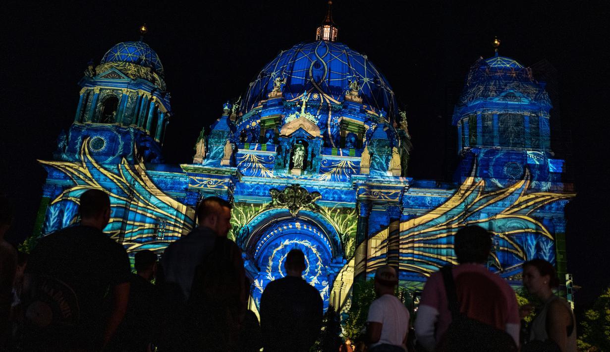 Orang-orang berkumpul di luar Katedral Berlin (Berliner Dom) yang diterangi cahaya dalam Festival of Lights di Berlin pada 14 September 2020. Kreasi cahaya lebih dari 90 karya seni tersebut ditampilkan di 86 lokasi yang berlangsung hingga 20 September mendatang. (John MACDOUGALL/AFP)