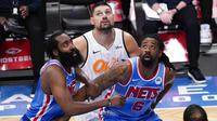 Pebasket Brooklyn Nets, James Harden dan DeAndre Jordan berusaha menghalau pebasket Orlando Magic, Nikola Vucevic, pada laga NBA, Sabtu (16/1/2021). Nets menang dengan skor 122-115. (AP Photo/Mary Altaffer)