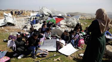 Anak-anak belajar di antara puing-puing sekolah mereka yang hancur di Desa Abu Nuwar, Tepi Barat, Palestina, Minggu (4/2). Hal itu dilakukan setelah tentara Israel menghancurkan sekolah mereka. (AP Photo/Mahmoud Illean)