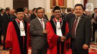 Menkopolhukam Mohamad Mahfud MD berfoto bersama Hakim Mahkamah Konstitusi (MK),  Suhartoyo dan Daniel Yusmic Pancastaki seusai pelantikan di Istana Negara, Jakarta, Selasa (7/1/2020). Keduanya akan bertugas dengan masa jabatan lima tahun ke depan. (Liputan6.com/Angga Yuniar)